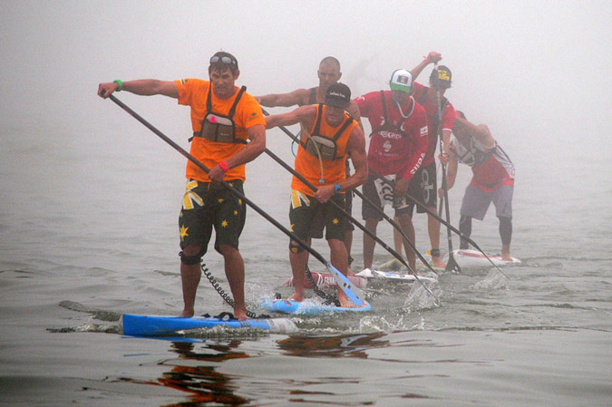 Australia's Jaime Mitchell led the pack during the foggy SUP Long Distance Race and won the Gold Medal in a dramatic and tense finish. Trailing Mitchell, from front to back are Kelly Margetts (AUS), Paul Jackson (NZL), Fernando Stalla (MEX) and Casper Steinfath (DEN). Photo: ISA/Tweddle