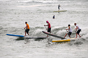 Jamie Mitchell (AUS), Fernando Stalla (MEX), Dylan Frick (RSA), and Ollie Shilston (GBR), from left to right, led the pack in Heat 1 of the Men's SUP Technical Race. Photo: ISA/Tweddle